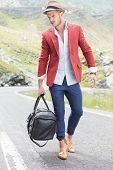 portrait of a young fashion walking on the road with a bag in his hand while looking down, away from