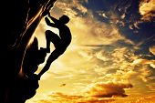 A silhouette of man free climbing on rock, mountain at sunset. Adrenaline, bravery, leader.