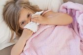 stock photo of high fever  - High angle portrait of a cute little girl suffering from cold as she lies in bed - JPG