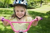 Close-up portrait of a little girl on a bicycle at summer park