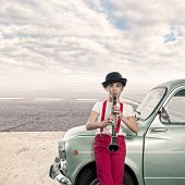 picture of clarinet  - little girl playing clarinet in an old car - JPG