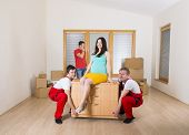 stock photo of movers  - Movers in new house with young family - JPG