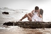 stock photo of brunette  - young sexy couple kisisng on beach rocks at sunrise - JPG