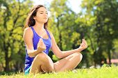 stock photo of stressless  - Young female athlete in sportswear meditating seated on a green grass in a park - JPG