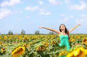 stock photo of sunflower  - Happy carefree summer girl in sunflower field in spring - JPG