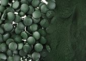 stock photo of algae  - Spirulina powder and tablets algae nutritional supplement heap surface close up top view - JPG