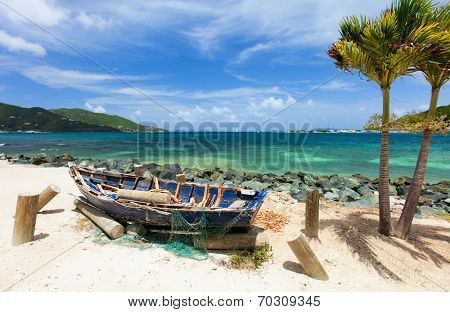 Old wooden boat at tropical coast with palm trees, white sand, turquoise ocean water and blue sky at Tortola, British Virgin Islands in Caribbean