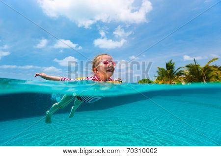 Split underwater photo of adorable little girl with yellow inflatable ring swimming in a pool on summer vacation