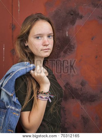 Pretty young girl with a denim jacket on a background of metall walls.