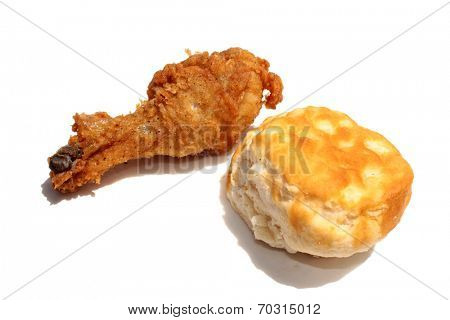 A fried Chicken Leg and Biscuit isolated on white with room for text. Fried chicken is enjoyed by people around the world. Flour Biscuit are good with fried chicken. The perfect Lunch or Dinner image.