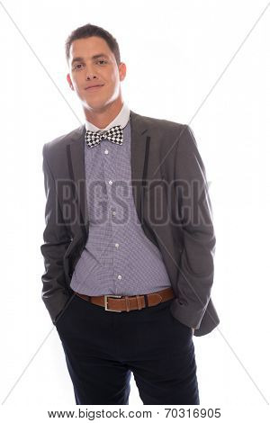 Smiling suave handsome young man in a bow tie posing confidently with his hands in his pockets smiling at the camera, three quarter on white