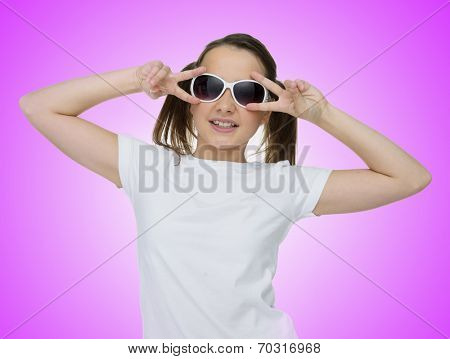 Smiling pretty young girl with her brown hair in pigtails wearing trendy sunglasses and giving the camera a friendly smile, on a purple studio background