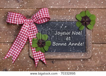 Chalk Board With Merry Christmas Message, Ribbon, Snowflakes And Clovers On Wooden Background - In F