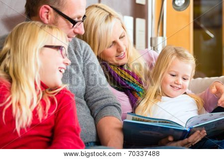 Family sitting together with mother, father and children comfortable on sofa, listening to fairy tale from story book