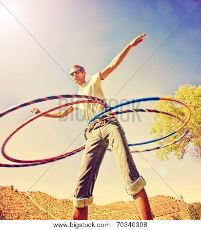 a young man hula hooping in a local park toned with a retro vintage instagram filter