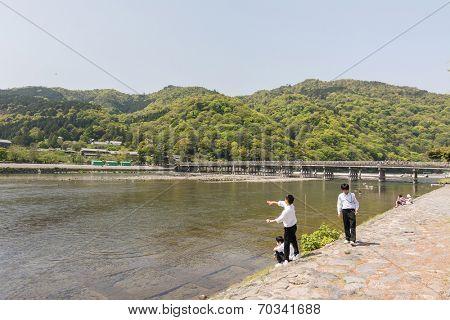 KYOTO, JAPAN - APRIL 26th  : Students throw stones at the shore of Hozu (Katsuragawa) River in Arashiyama in Kyoto, Japan on 26th April 2014.