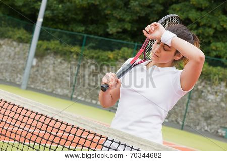 Pretty tennis player wiping her brow on a sunny day