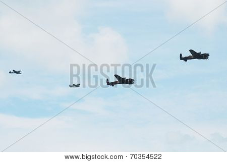 EASTBOURNE, ENGLAND - AUGUST 14, 2014: Lancaster bomber PA474 of the Battle of Britain Memorial is followed by Canadian Lancaster KB726 and Spitfire and Hurricane fighters at the Airbourne airshow.