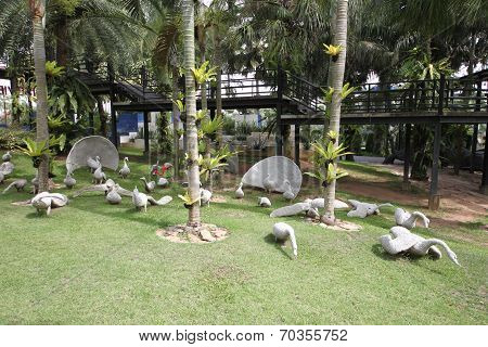 A meadow with white swans and grass and trees and stones in the Nong Nooch tropical botanic garden n