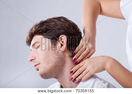 Physiotherapist Palpationing Patient With Stiff Neck