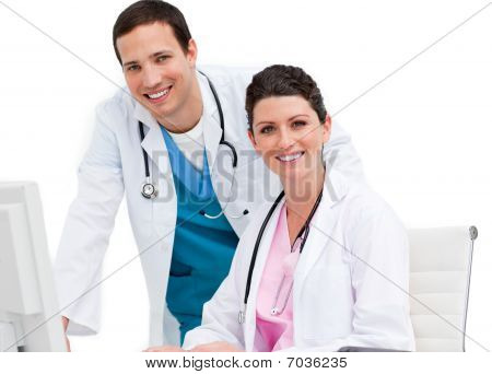 Two Smiling Doctors Working At A Computer