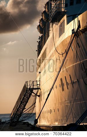 View along the dock and side of the ship of a metal passenger staircase and gangway on a cruise liner fro embarking and disembarking with an ocean bacldrop at sunset