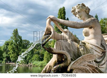 Detail of a classical stone fountain with a robed maiden holding an urn spilling a jet of cascading water into the lake below