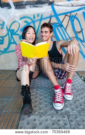 Young Multi-ethnic Couple Reading A Book.