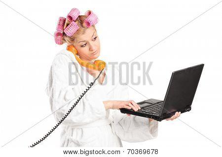 Woman in bathrobe talking on phone and working on laptop isolated on white background