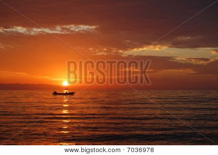 Sunset over small power boat