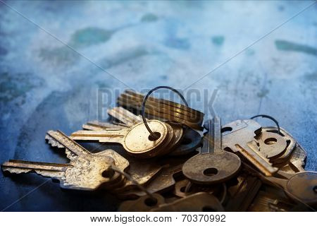Mound of Gold keys on a bluish old metal background.