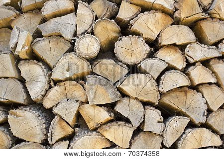 Firewood Stacked In The Woodpile. Industrial background.