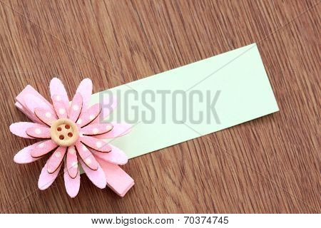 Pink Artificial Flowers And Note Paper Stuck On Dark Wood.