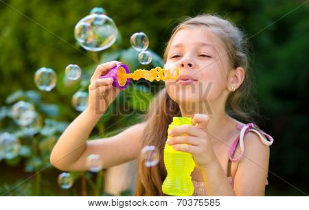 Cute little girl is blowing a soap bubbles, outdoor shoot