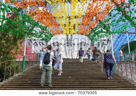 Tourists Climbings Stairs With Flower Decorations Of Church In Madeira, Portugal.