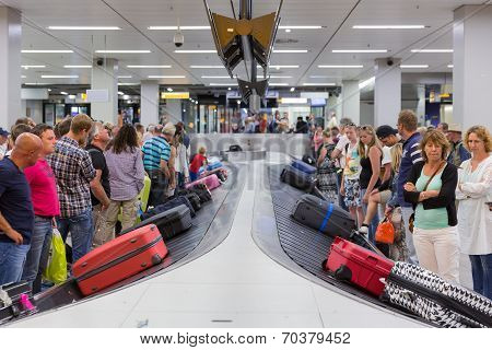 Airplane Travelers Waiting For Their Luggage At Schiphol Airport In Amsterdam, The Netherlands