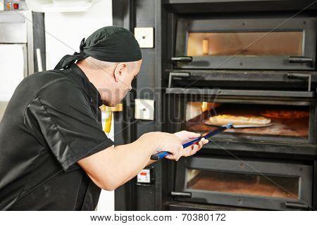 chef baker in uniform making pizza at restaurant kitchen stove