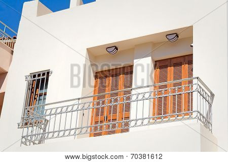 Fragment Of A Facade Of A House With A Balcony And Blinds From The Sun.