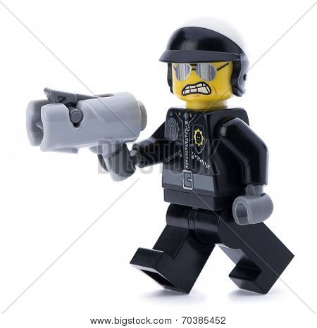 Ankara, Turkey - March 15, 2014 : Lego movie minifigure character bad cop with gun walking isolated on white background.