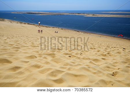 PILAT, FRANCE - JUNE 27, 2013: Paragliders and tourists on the dune of Pilat. This dune is the biggest one in Europe, and it still grows