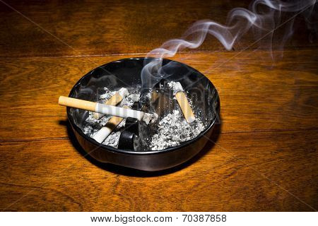 A burning cigar in a classic black ashtray streaming smoking in a dark, moody setting.  The smoke is real, straight from the cigarette and not put in later during post processing.