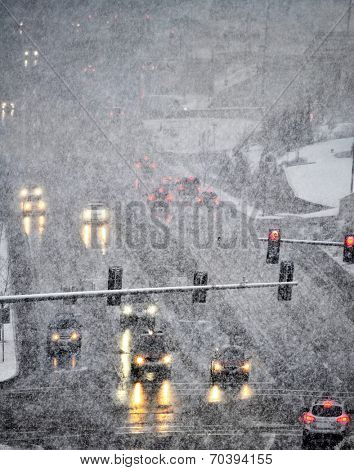 Snowy winter road with several cars driving on roadway with traffic lights