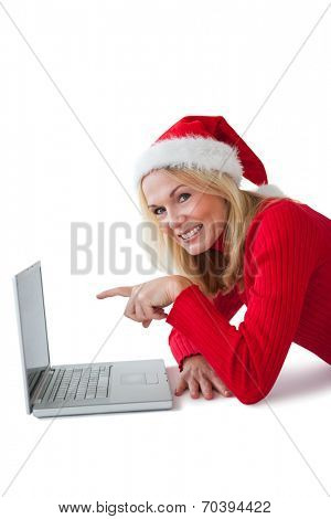 Festive blonde smiling at camera and pointing to laptop on white background
