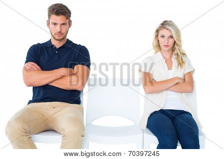 Young couple sitting in chairs not talking during argument on white background