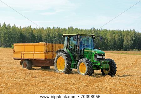 Farmer Driving John Deere 5820 Tractor And Trailer