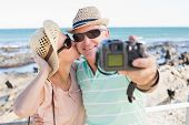 picture of take off clothes  - Happy casual couple taking a selfie by the coast on a sunny day - JPG