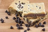 stock photo of chocolate-chip  - Chocolate chip cookie bars on a wooden surface with chocolate chips in the forground - JPG