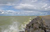 foto of dike  - Clouds and storm over a dike in a lake  - JPG