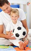 Smiling Little Boy And His Father Playing With A Soccer Ball