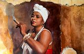 picture of graffiti  - Graffity of Woman wearing a head scarf and traditional jewellery smoking a big fat Cuban cigar with a look of relish and defiance against an old grunge graffiti painted brown wall - JPG